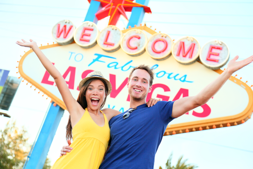 Las vegas people - couple happy cheering by sign. Welcome to Las Vegas sign billboard and excited cheerful young multiracial couple having fun on the strip during travel holiday vacation, Nevada, USA.